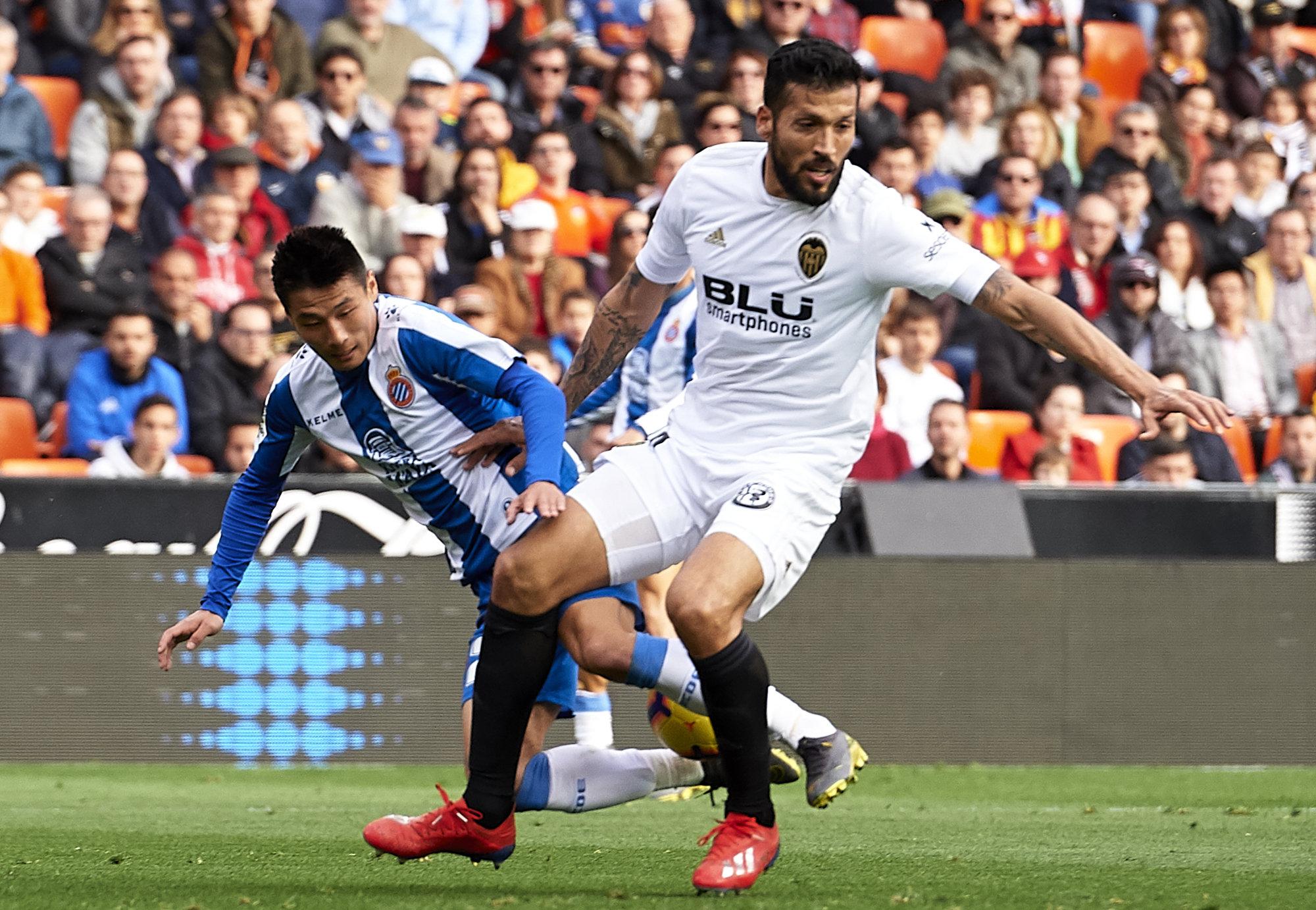 Garay pugna por el cuero con Wu Lei en un lance del Valencia-Espanyol.
